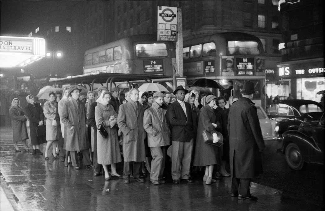 A long queue of people waiting in the rain for their bus captures the eye of Collins as part of his focus on commuter travel and rush hour in London's streets and rail network. The low light and wet conditions make for an atmospheric image.