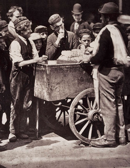 This photograph was one in a series of social documentary photographs taken by John Thomson and published in Street Life in London. Here Thomson shows customers gathered round the barrow of an ice cream seller. By the 1870s London's ice cream and flavoured ice trade was exclusively in the hands of the Italian community who lived in Clerkenwell and Saffron Hill.