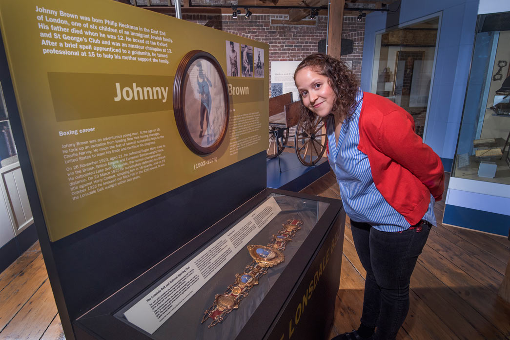 Lauren Johnson of the Jewish Museum stands next to Johnny Brown's Lonsdale Belt.