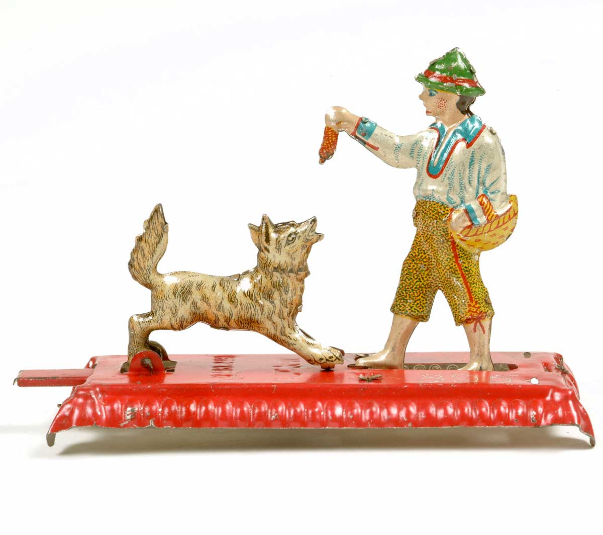 This mechanical penny toy, a lithographed tinplate figure of a boy holding a scrap of meat above an excited dog, is operated by a spring-loaded lever.