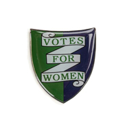 A purple and green shield-shaped 'Votes For Women' pin badge