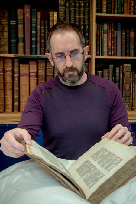 Librarian holds a rare medieval manuscript.