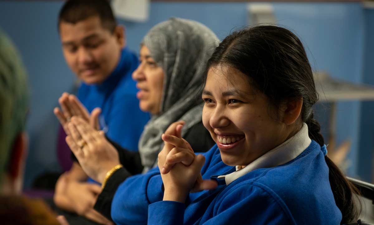 A female student in a blue uniform smiles and claps in one of our learning spaces.