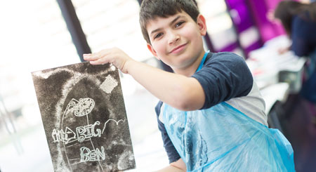 A school student holds up a piece of work created in a facilitated art session at the museum.