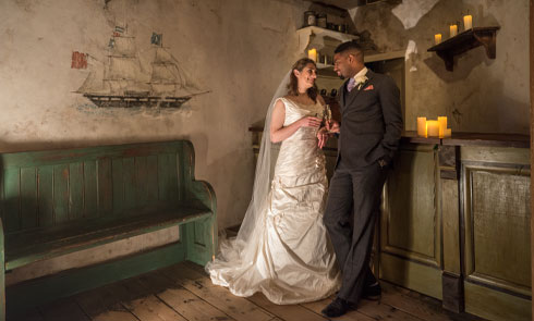 bride and groom pose in the museum of london docklands