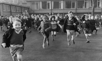 Children running across the school playground towards photographer Henry Grant. The school was the Highbury Quadrant Infants School in Islington. (c) Henry Grant Collection / Museum of London.