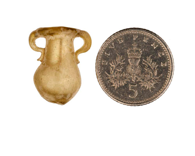 A miniature Roman model of a vase, carved designed to catch tears, photographed next to a 5 pence coin for scale.
