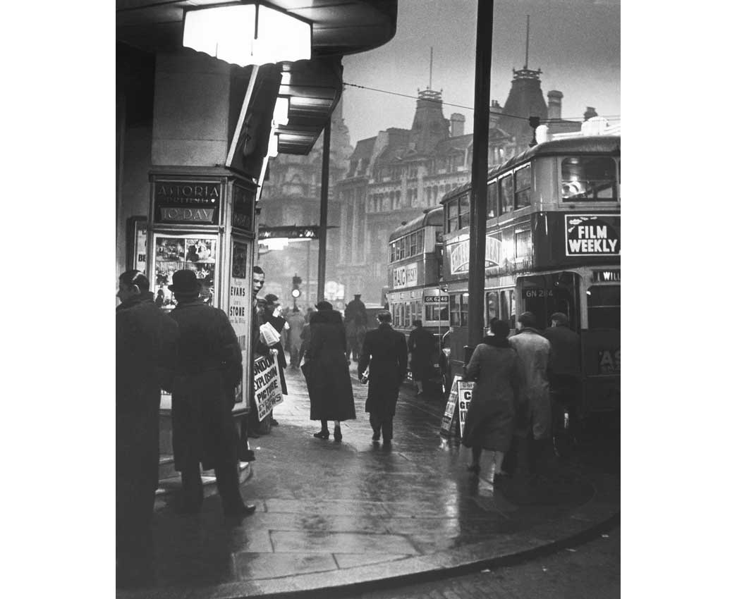 Charing Cross Road, c. 1935. Evening street scene outside Foyles book shop. Charing Cross Road is renowned for its specialist and second-hand bookshops. Suschitzky was attracted by the extensive array of second-hand bookshops and teahouses, and the crowds that flocked to them. The resulting series of photographs are amongst Suschitzky's most acclaimed work.