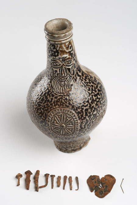 17th century stoneware Bartmann jug (also known as a Bellarmine) made in Frechen, Germany. It has been re-used as a witch bottle. It was found with a heart-shaped piece of felt pierced with pins and eleven nails inside. This would have been a charm to prevent witchcraft. The bottle is decorated with a bearded face mask on the neck and a rosette medallion on the body.