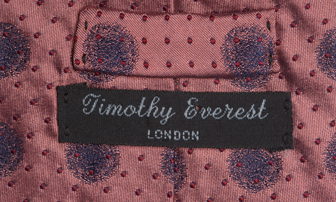 Close up of label of a Timothy Everest tie worn by Francis Golding