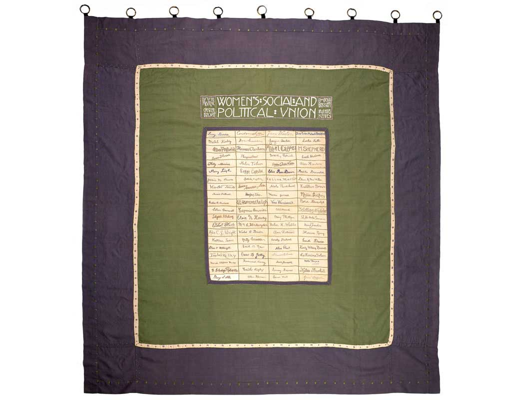 Suffragette banner composed of 80 rectangular pieces of linen sewn together and bordered by green and purple panels. The 80 pieces of linen are embroidered in purple cotton with the signatures of eighty Suffragette hunger-strikers who, by 1910, had 'faced death without flinching'. Along the top is embroidered 'Women's Social and Political Union' in Scottish art nouveau style along with the names of the suffragette leaders Emmeline and Christabel Pankhurst and Annie Kenney. The banner was first carried in the 'From Prison to Citizenship' procession in June 1910 to symbolise the spirit of comradeship that gave suffragette prisoners the strength and courage to endure hunger strike and force feeding.