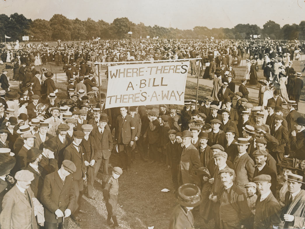 A WSPU rally in Hyde Park in support of the Conciliation Bill, 23 July 1910. This group of male supporters is making its way to one of the four platforms for men's groups. If the Conciliation Bill had been passed by Parliament it would have given the vote to women who occupied premises for which they were responsible. Single women would have been the greatest beneficiaries of such a Bill.