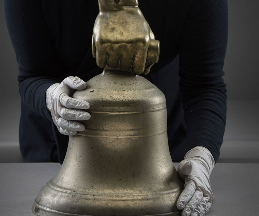 Prison bell from Holloway prison, a large brass hand holds the top of the bell