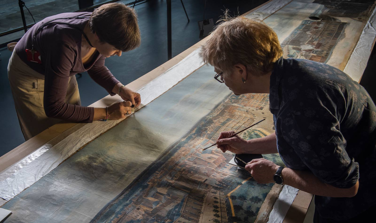 Two female conservators work on a long stretch of panorama, cleaning it with small brushes.
