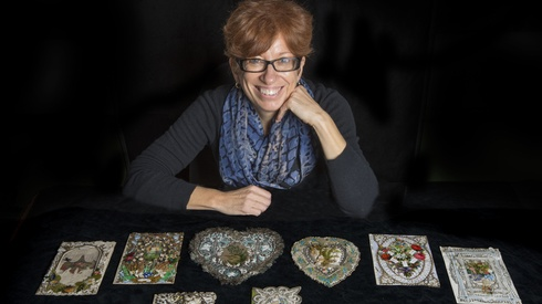 A woman sits at a table displaying some of the museum's collection.