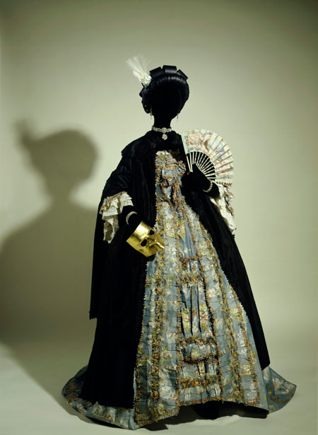 A black silk domino cloak with gold mask, worn over a french silk and linen dress c.1765