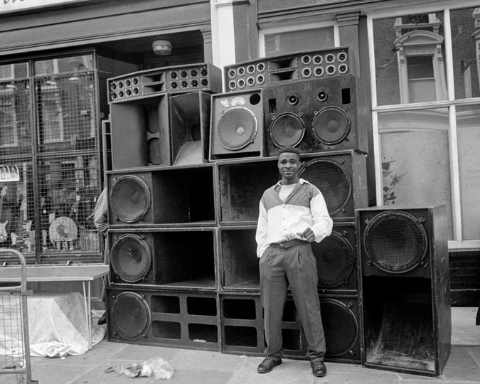 A sound system photographed with a young man standing next to it at the Notting Hill Carnival.