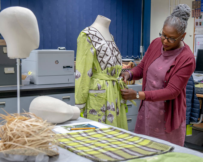 Iyamide Thomas inspects a dress before it goes on display.