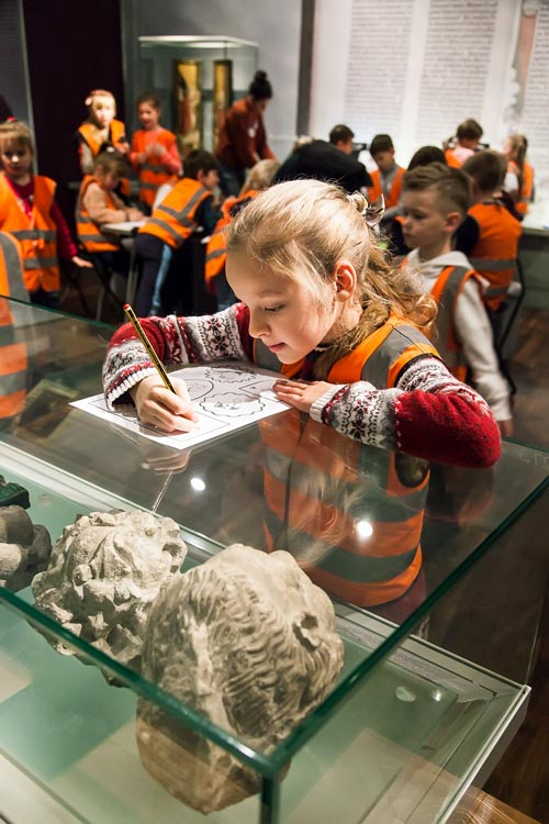 A girl from a supplementary school leans on a display case containing pieces of Roman statues while drawing on a sheet of paper.