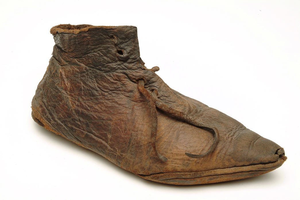 Small leather shoe with a pointed toe and leather laces. The upper part of the shoe is made from one single part of leather. This shoe is lightweight, flexible with a thin sole. During the medieval period children's shoes were similar to those worn by adolescents and adults. The only exceptions were the exaggerated, long, pointed 'poulaines', which were only worn by adults. This child's ankle-shoe dates to the late 1300s. It is fastened at the front with a leather thong. It was found at Baynard's Castle Dock, near Blackfriars, London.