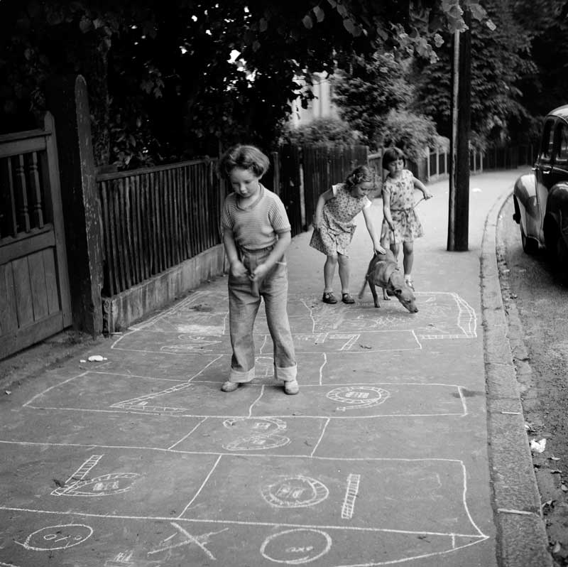 A black and white photo of three young girls and a dog on a pavement that they have drawn on with chalk.