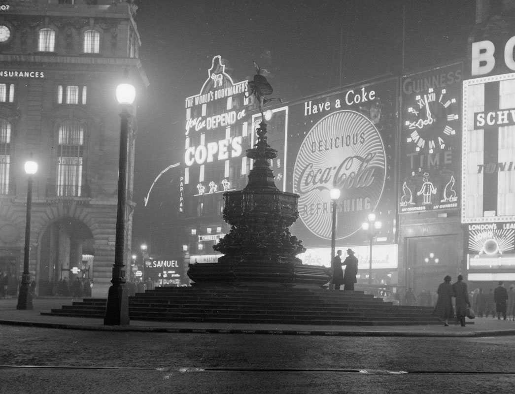 The statue of Eros in Piccadilly with the advertising lights in the background. The first illuminated advertising boards were built here in 1910 and Coca Cola, whose sign can be seen here, have the longest continuous presence at Piccadilly with an advert here continually since 1955. The Guinness Clock advert which can also be seen, was installed in 1955 and was the first of a number of legendary Guinness adverts to have moving parts. As well as a clock face it featured a zoo keeper with 2 juggling sea lions. The clock face was replaced in 1959.