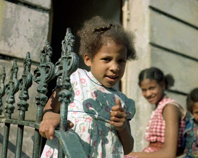 A young girl holding onto railings on a residential street. This photograph is from a series of street scenes by Paul Styles taken in and around the Notting Hill area, often featuring members of the local black community.