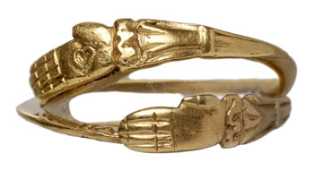 Beautiful image (Picturechase no 000742) of a post-medieval gold gimmel ring with interlocking gold hands and bezel. Shown closed. When open, the ring has an inscription that reads: 'As hands do shut soe hart be knit', reveling a secret shared by the wearer and her lover.