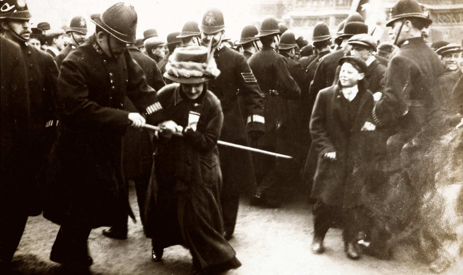 A Suffragette struggling with a policeman on Black Friday 18 November 1910. Furious suffragettes marched on the House of Commons in response to delays to the Conciliation Bill. The resulting riot ended in the arrest of 115 women and four men. Many of the protestors suffered violence, intimidation and even acts of indecency at the hands of the police. One suffragette noted 'Several times constables and plain-clothes men who were in the crowds passed their arms round me from the back and clutched hold of my breasts in as public a manner as possible, and men in the crowd followed their example...My skirt was lifted up as high as possible, and the constable attempted to lift me off the ground by raising his knee. This he could not do, so he threw me into the crowd and incited the men to treat me as they wished'.  < ...Read more