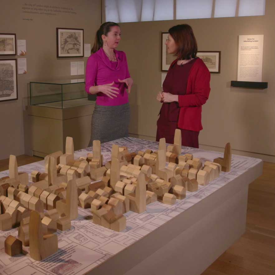 Meriel and Nina discuss the rebuilding of London above a large wooden diorama of the city.