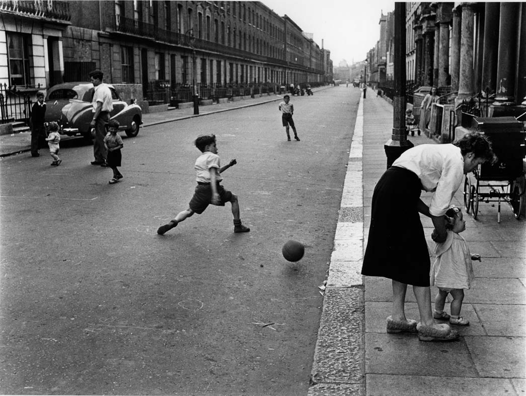 Southam Street, North Kensington, with boys playing football, 1956. Before the replacement of terraced houses by tower block estates and the rapid growth of car ownership, streets like this were communal spaces and playgrounds for children and adults alike.