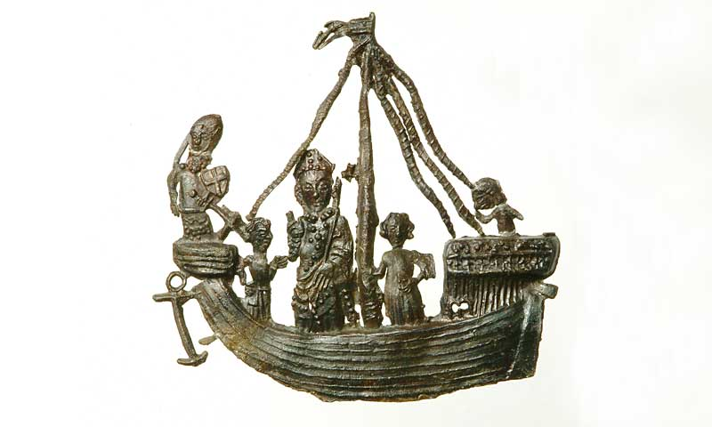 Pewter pilgrim badge of St Thomas Becket standing on a ship. A knight in armour stands at the front of the ship. Two figures stand next to Becket on the deck and a sailor at the stern. This badge depicts the return of St Thomas Becket from exile in France in December 1170, only a month before his murder. This anniversary was commemorated every year at Canterbury with a festival known as the Return of St Thomas, 'Regressio Sancti Thomae'. Here he is shown on board the ship with three companions: a knight, a clerk holding a book, and a third standing next to St Thomas. The knight's shield is charged with a cross. A sailor attends to the rigging in the stern of the ship.