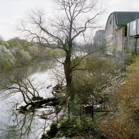 Colour pigment photographic print showing the Old River Lea looking south from the bridge connecting the Manor Garden Allotments to Waterden Road in Stratford, 2007. The allotment plotholders were amongst those evicted when this area was cleared to make way for the Olympic Park. This photograph was taken as part of a project to document the site of the London 2012 Olympic Games prior to its closure for redevelopment in July 2007.