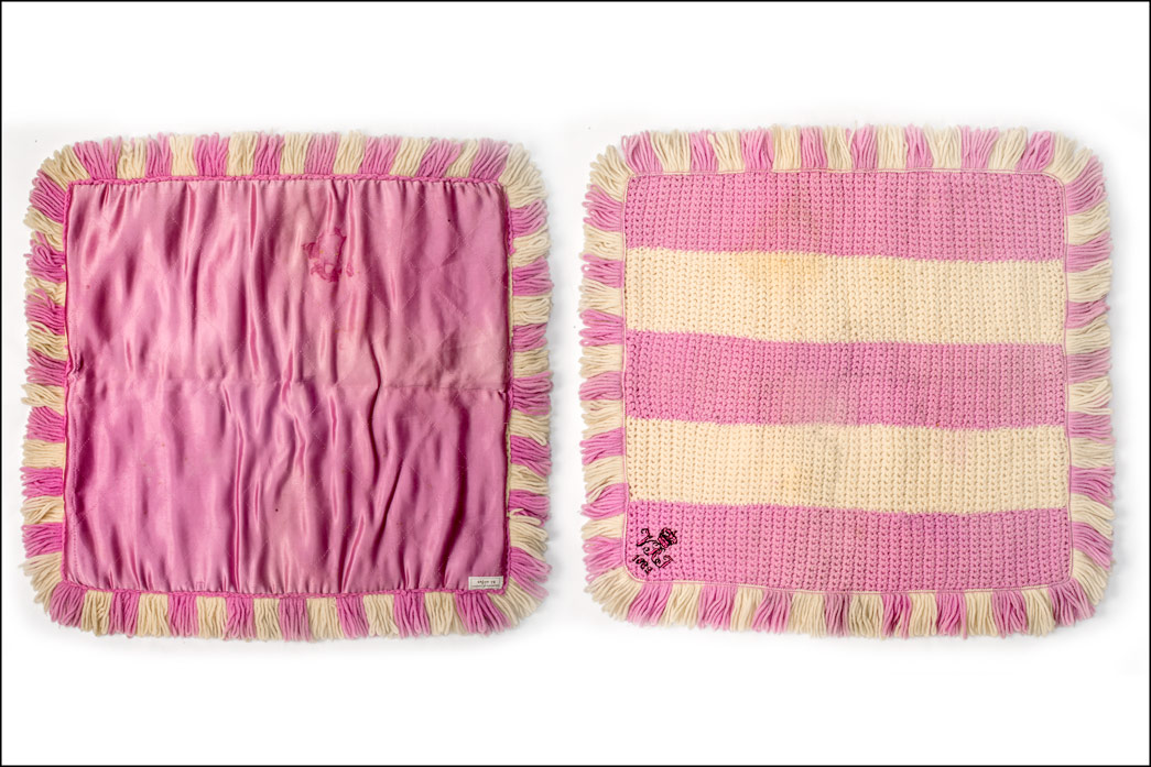 Blanket crocheted in deep pink and off-white wool, faced with quilted deep pink satin. Embroidered in one corner with 'VRI 1883'. Said to have been made by Queen Victoria for Princess Alice, Countess of Athlone (1883-1981), last surviving granddaughter of Queen Victoria. Her father was Prince Leopold, Duke of Albany (1853-1884), the youngest son of Queen Victoria and Prince Albert. The blanket was in Princess Alice's possession when she died.