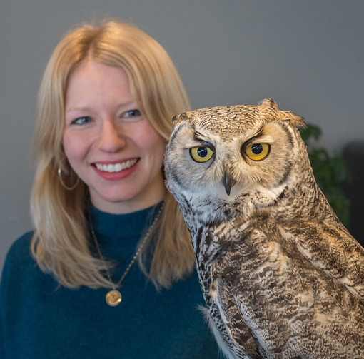 A blonde woman, Jennie Webber, smiling and holding an owl.