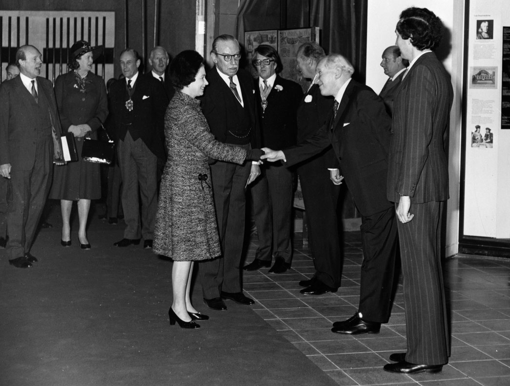 H.M. The Queen is greeted by Mr. Tom Hume , Director of the Museum of London, as she arrives to open the new museum, on Thursday 2nd December. With the Queen is Lord Harcourt, Chairman of the Board of Governors of the Museum of London. Others are L-R Sir Martin Charteris, Private Secretary to the Queen, Mrs Dugdale, Lady in Waiting, the Lord Mayor, Sir Robin Gillett, The City Remembrancer Lord Posonby, Chairman of the GLC Lord Donaldson, Ministers for the Arts, Mr Leslie Whatley, Mr Max Hebditch, Deputy Director, Museum of London.