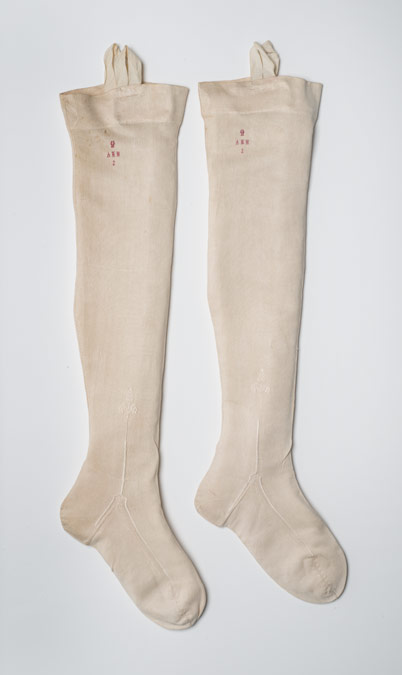 Pair of white silk stockings with the initials A.M.M. and a crown embroidered below the top. Said to have belonged to Princess Alice Maud Mary (1843-1878), the second daughter of Queen Victoria, when a child.