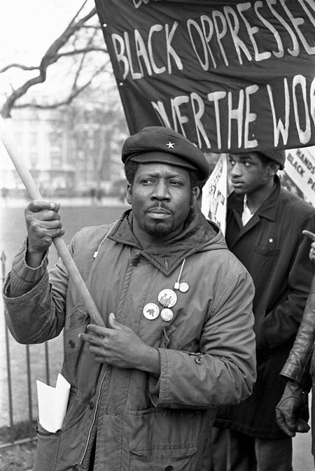 This photograph by Neil Kenlock, the official photographer to the British Black Panther movement, depicts demonstrators during a Black Panther rally. Several men are seen walking with badges and banners along a street in London, protesting against 'BLACK OPPRESSION'.