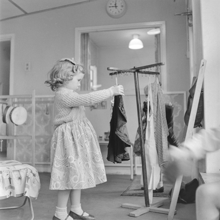 Henry-Grant--A-young-girl-playing-dressing-up-at-Sumner-Nursery-School,-Peckham,-1959.jpg