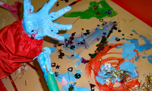 A child's paint-covered hand at a messy play session.