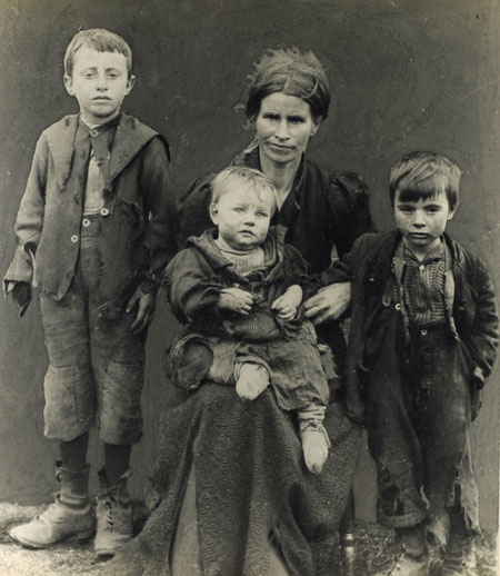 A poverty stricken East End family, circa 1900. A mother with her three children, all dressed in rags.