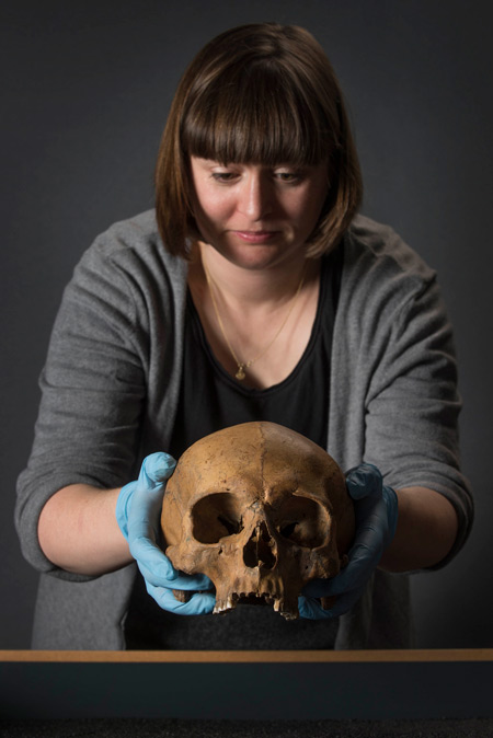 An osteologist at the Museum of London holds a Roman skull.