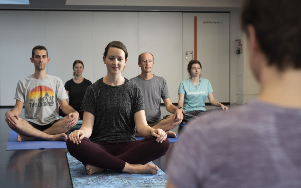 Staff sitting on yoga mats during a Museum of London yoga class