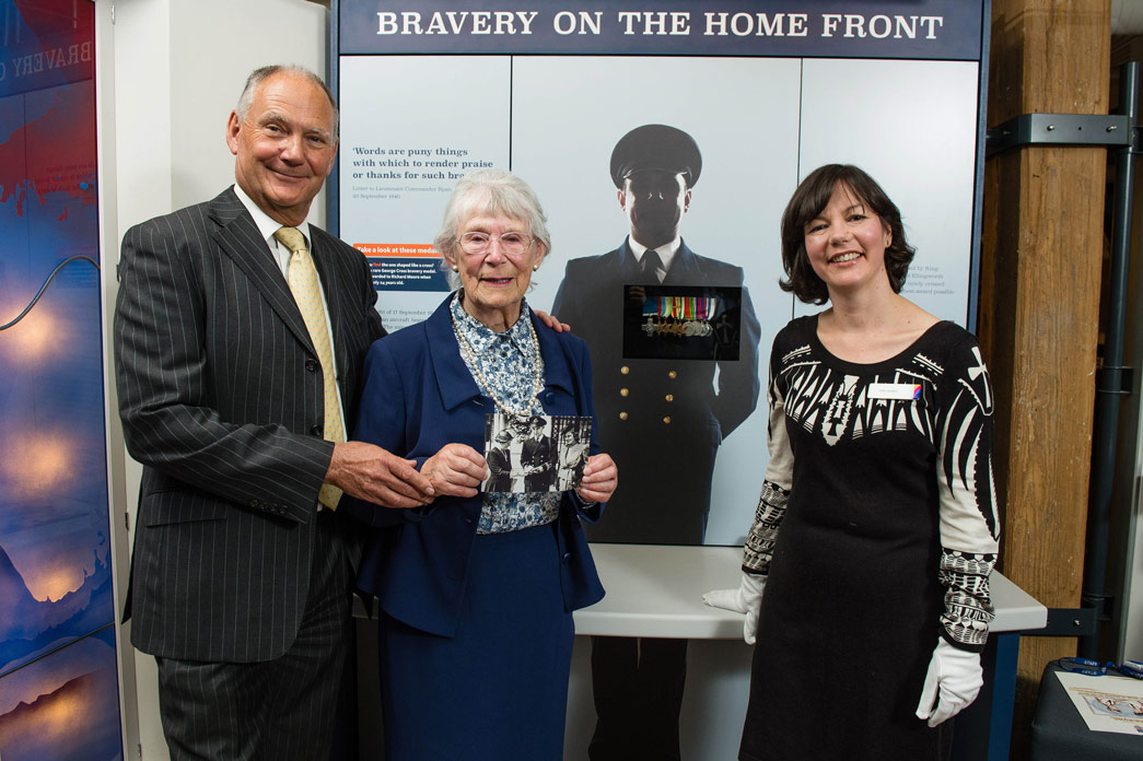 Members of Richard Moore's family stand in front of a display of his medals, with curator Vyki Sparkes.