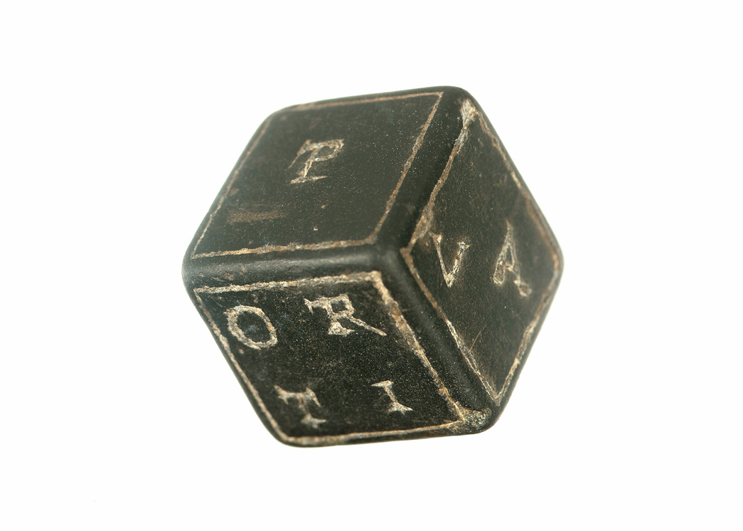 Cube of basalt stone with carved capital letters on each side. The lettering is picked out on lead or silver. Each side bears a combination of letters corresponding to the numbers on a normal die.