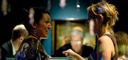 Two women chatting at a Friends evening event in a gallery.