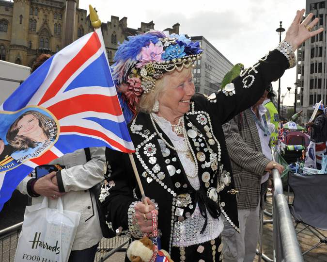 A Pearly Queen waves a flag at the passing wedding parade of William and Kate.