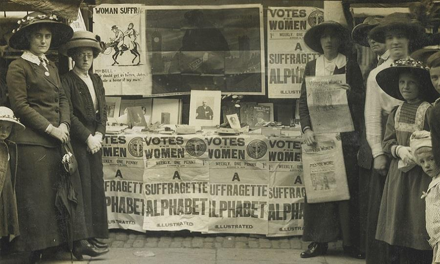 Women and girls stand around a suffragette fundraising stand holding 'Votes for women' posters