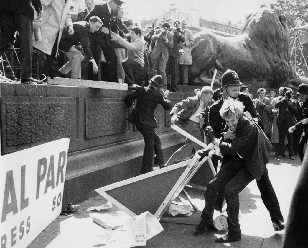 Clashes at a Mosley riot in Trafalgar Square between supporters, protestors and the police, c. 1960. Sir Oswald Mosley was a leader of the British fascist movement. A prominent figure before the Second World War, he stood at the 1959 general election for Kensington North, shortly after the 1958 Notting Hill race riots, and again at the 1966 general election, this time for Shoreditch and Finsbury. However, opposition to fascism was strong in post-war Britain and on both occasions he polled few votes.