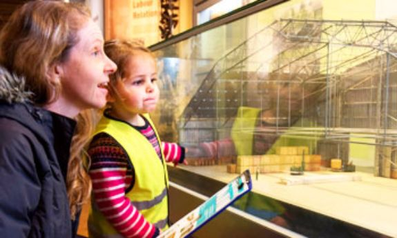 A parent and small child using an activity trail in a gallery.